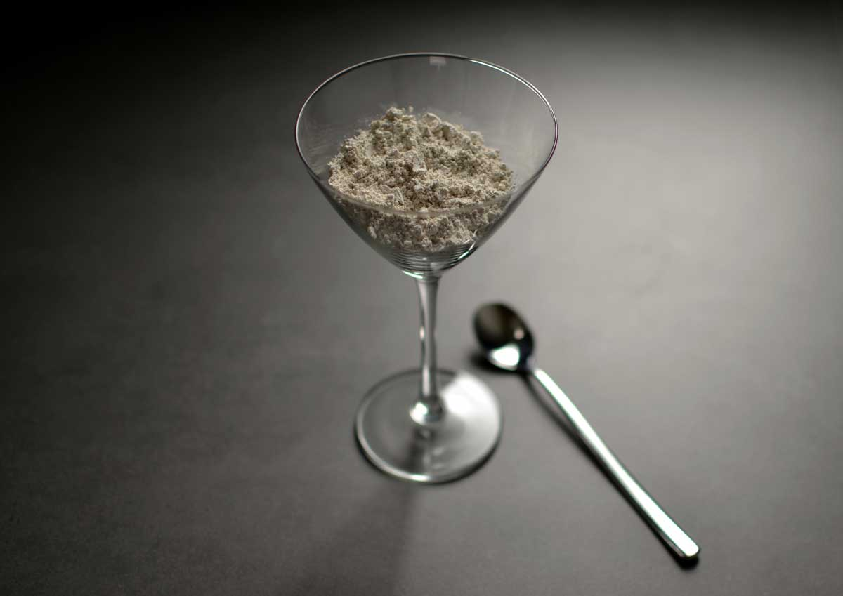 How Much Diatomaceous Earth Should I Take? A glass with a spoon